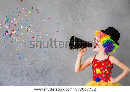 Photo of  Let's party! Funny kid clown. Child speaking with megaphone. 1 April Fool's day concept