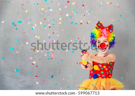 Let's party! Funny kid clown playing at home. Child shooting party popper confetti. 1 April Fool's day concept