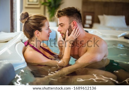 Let's stay here forever. Young couple in hot tub.