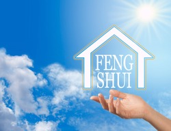 Let the Enlightened Wisdom of Feng Shui into your Home - female hand with a house shape containing the words FENG SHUI floating above against a blue sky background with a bright sun shining down