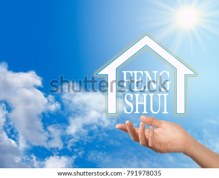 Let the Enlightened Wisdom of Feng Shui into your Home - female hand with a house shape containing the words FENG SHUI floating above against a blue sky background with a bright sun shining down #791978035