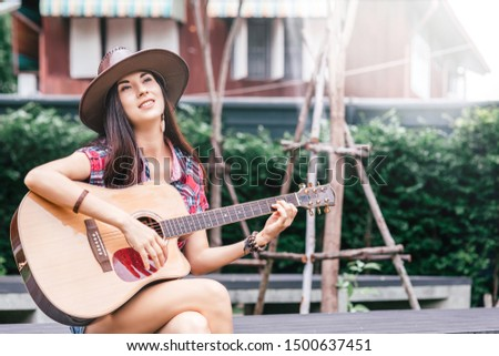 Let the melody take you away. Beautiful cowgirl singer perfoming outdoors. Copy space on the right side