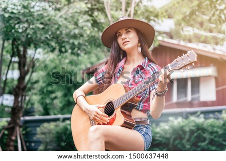 Let the music speak. Beautiful cowgirl singer perfoming outdoors. Copy space on the left side
