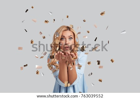 Let the party begin. Playful young woman blowing confetti and looking at camera while standing against grey background #763039552