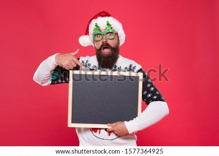 Let this surprise you. Surprised santa point finger at blackboard. Bearded man prepare surprise party. Holiday surprise. New year and Christmas surprise, copy space.