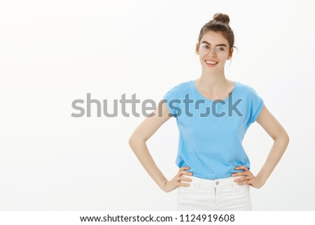 Let us get it started. Portrait of happy confident young woman in bun and glasses, holding hands on hips and smiling broadly, being ready to work hard, feeling joyful and positive over gray background