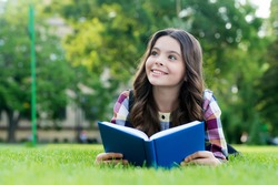 Let your creative ability investigate. Happy child read book lying on green grass. Reading education. Book learning. School library. Literature lesson. Imagination and fantasy. Knowledge day.