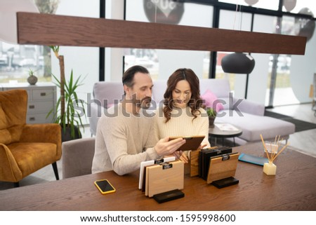 Lets discuss. Man and woman in light sweaters discussing wood samples