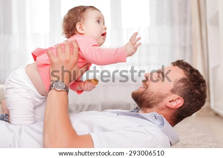 Lets fly. Nice agreeable father holding the baby and looking at it while playing on floor