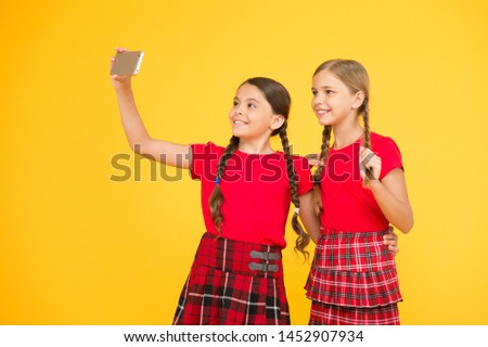 lets make pic. girls in uniform. small girls making selfie on phone. having fun. sisterhood and friendship. happy knowledge day. childhood happiness. education concept. back to school. social network.