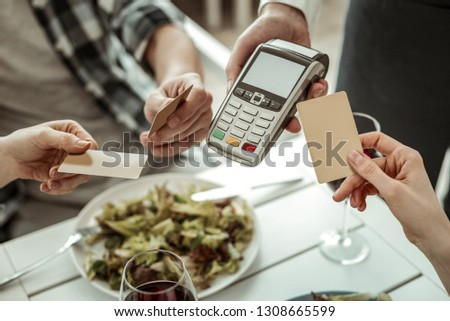 Lets pay. Competent waiter serving his clients and holding terminal for payments