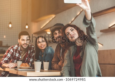 Lets remember this moment. Cheerful young woman is making selfie with her friends on smartphone. They are sitting at table in cafe and smiling