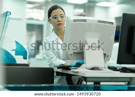 Lets work. Serious brunette woman wearing protective glasses while concentrating on task #1493930720