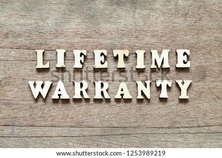 Letter block in word lifetime warranty on wood background #1253989219