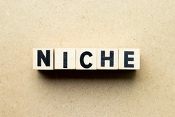 Letter block in word niche on wood background