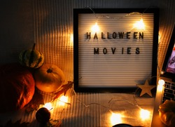 letter board on sofa with pumpkins and garland . Halloween movie .pumpkins ,close up , flat lay autumn decoration