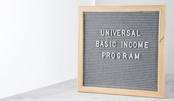 Letter board with words Universal Basic Income Program. Announcement government support program