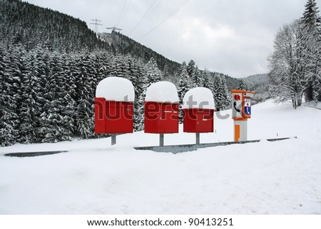 Letter boxes are covered with snow beside an SOS phone device in a remote mountain village