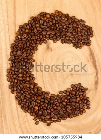 Letter C, alphabet from coffee beans. isolated on wood