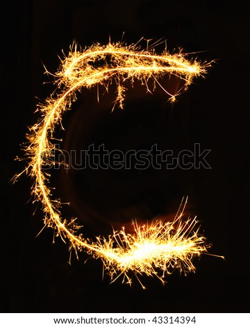 Letter C made of sparklers isolated on black