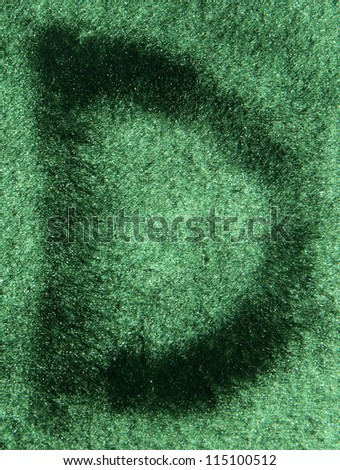 Letter D on a fluffy green texture close view