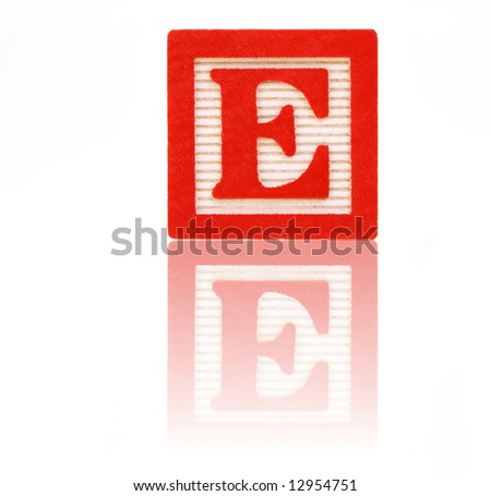 letter e in an alphabet wood block on a reflective surface