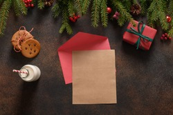 Letter for Santa Clause, milk, and homemade gingerbread cookies on dark background. View from above. Space for text.