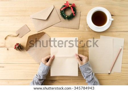 Letter for Santa. Female hand holding blank letter paper on wooden table  with cup of tea and Christmas decorations