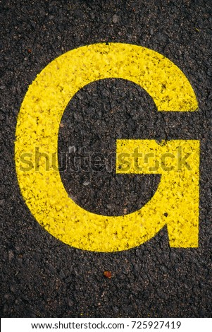Letter G on asphalt road, top view #725927419