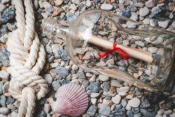 Letter in bottle lying on seashore with marine rope and seashells