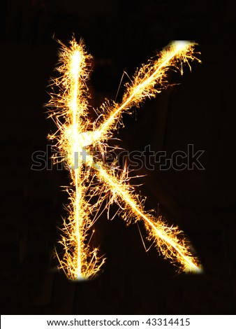 Letter K made of sparklers isolated on black