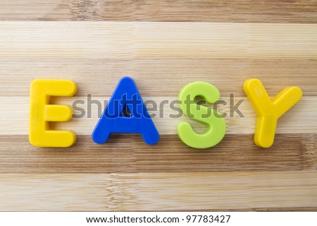 "Letter magnets ""EASY"" closeup on wood background"
