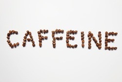 Letter of CAFFEINE arranged with coffee beans on white background with some space for your text