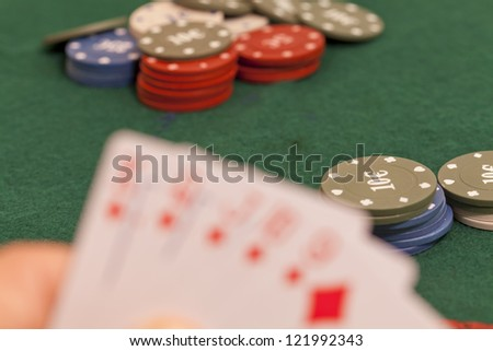 Letter on a green felt poker and play with their chips