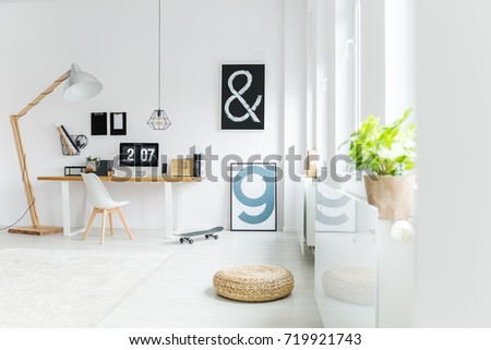 Letter posters, wicker pouf and plants in scandinavian study workspace #719921743