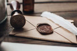Letter seal with wax seal stamp on the wood table. Vintage notary stamp and sealed envelope. Post concept. Sealing wax. Wax seal. Dark academia style. Scandinavian hygge styled composition.