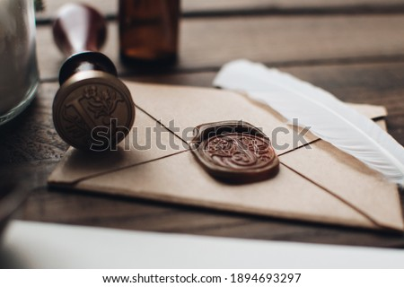 Letter seal with wax seal stamp on the wood table. Vintage notary stamp and sealed envelope. Post concept. Sealing wax. Wax seal. Dark academia style. Scandinavian hygge styled composition. Foto stock ©