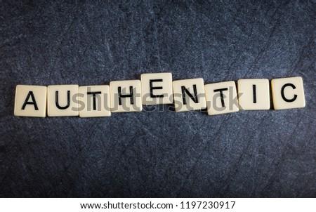 Letter tiles on black slate background spelling Authentic