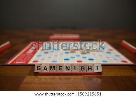 Letter tiles spelling out the words game night on stand in the foreground with out of focus game board in the background. Stockfoto ©
