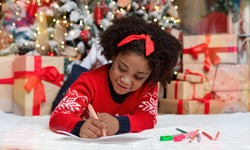 Letter to Santa. Cute little black girl lying on floor and writing wish list of presents for Christmas in decorated room