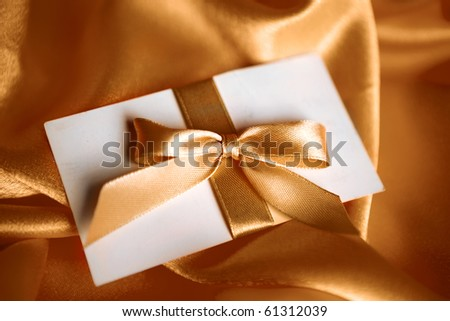 letter with golden ribbon on red satin