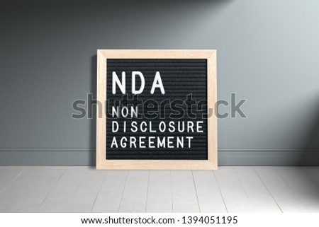 """Letterboard with acronym NDA for """"non disclosure agreement"""" in front of a wall #1394051195"""