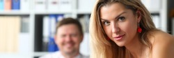 Letterbox view of blonde attractive woman standing at office workplace looking in camera portrait