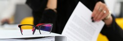 Letterbox view of nice modern black red glasses lie down on important paper pack in office closeup