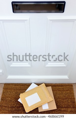 Letters and a package lying on a doormat, blank labels to add your own name and address, focus on the letters.