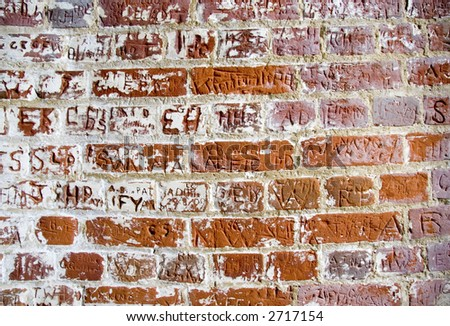 Letters carved in a bricks wall