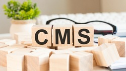 letters cms cube wood on wooden table white background, business concept. CMS short for content management system