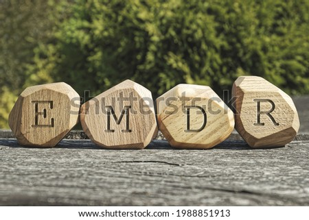 Letters EMDR written on wooden irregular blocks. Eye Movement Desensitization and Reprocessing psychotherapy treatment concept. Foto stock ©