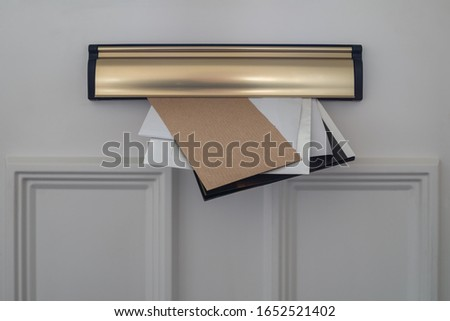 Letters, flyers  and utility demands, posted through a domestic letterbox. Paper waste reduction concept. Stock photo ©
