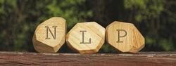 Letters NLP written on wooden irregular blocks. Neuro-linguistic programming concept.